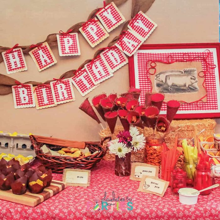 birthday party food buffet with vegetables a happy birthday banner and a rustic farm animal photo