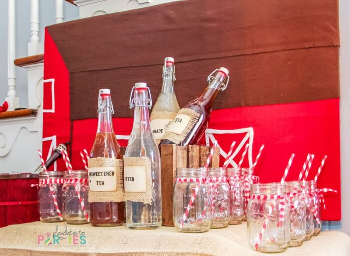 a drink buffet with a backdrop that looks like a red barn, mason jars with red paper straws and red gingham tied around the openings