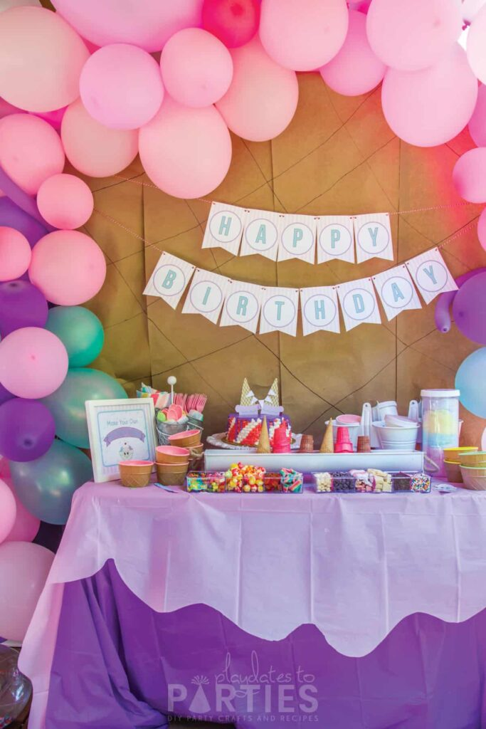 Ice cream birthday party buffet with balloon garland and happy birthday banner