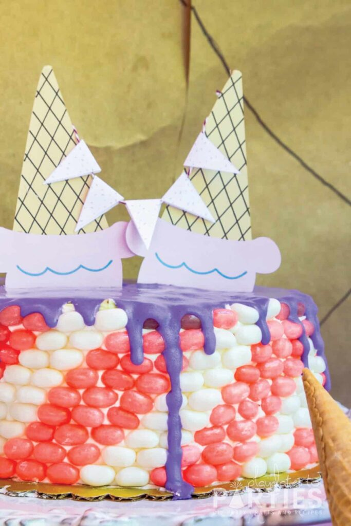 cake decorated with pink and white stripes made out of jelly beans with ice cream cone toppers