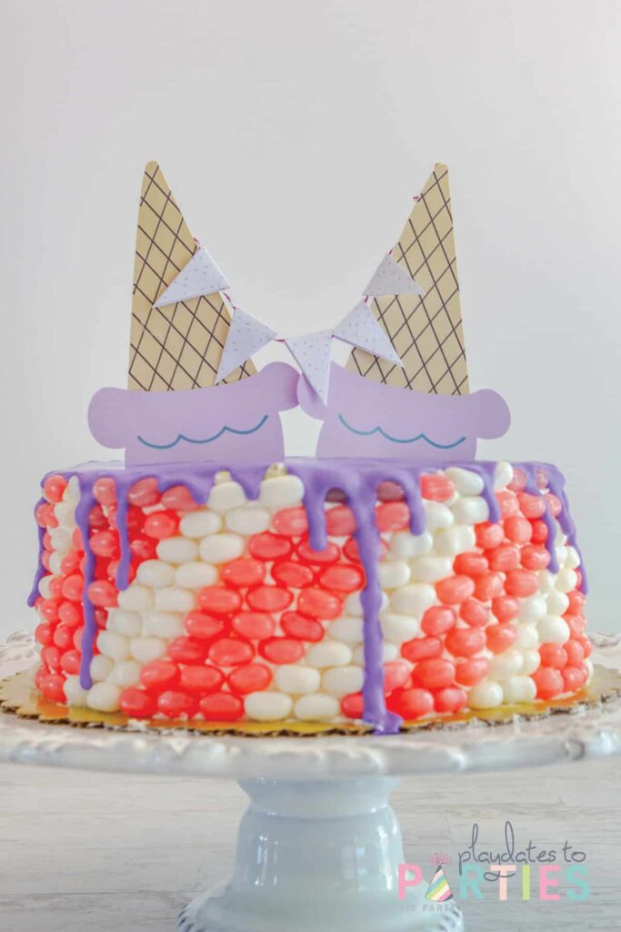 cake on a white cake stand with purple frosting and ice cream cone toppers