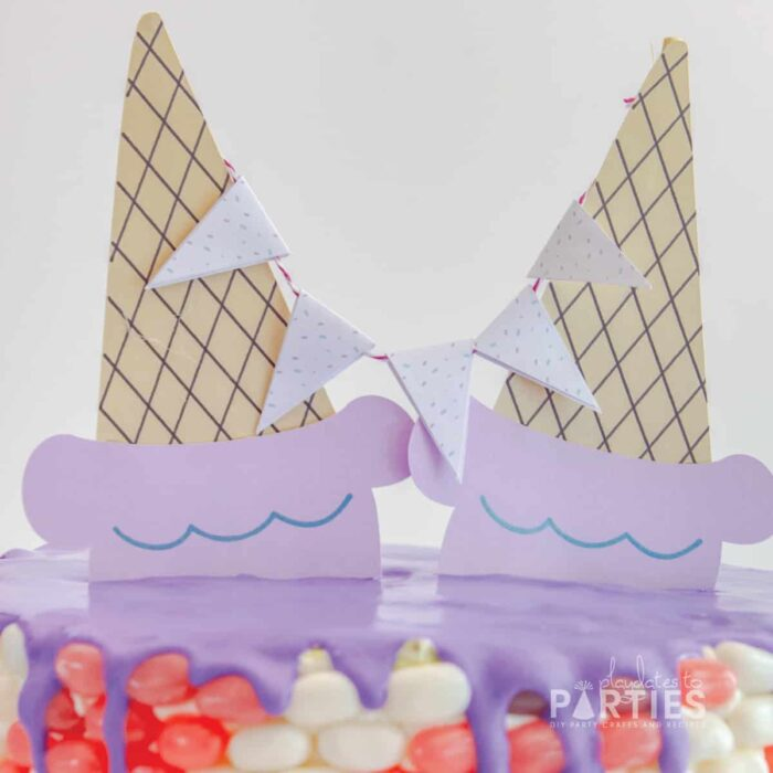 close up of two paper ice cream cone decorations on top of a cake