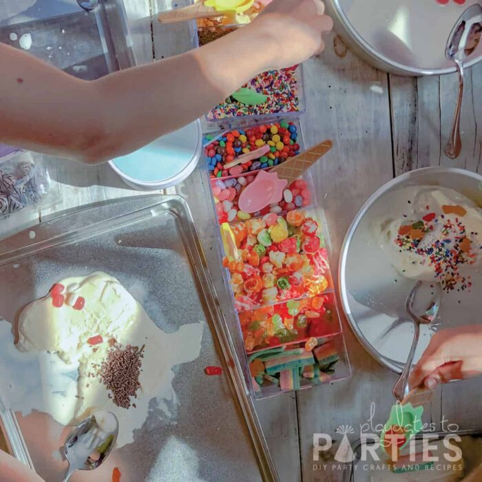 overhead view of children mixing candy and treats into ice cream