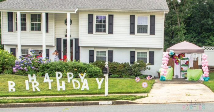 photo of a house with giant yard letters spelling happy birthday and a tent in the driveway with flower decorations