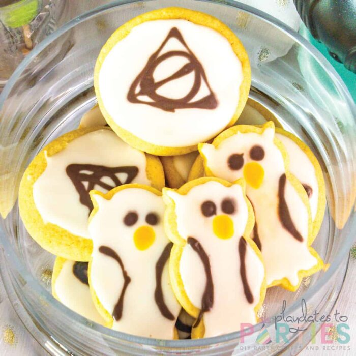 Sugar cookies shaped and decorated to look like the deathly hallows and white owls
