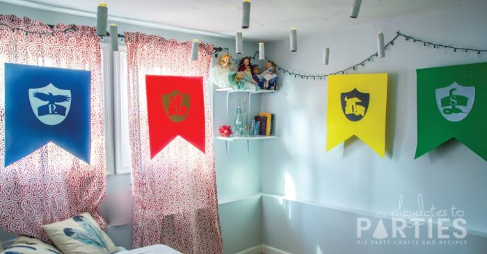 A room with Hogwarts house banners in blue, red, yellow, and green, with floating candles and twinkle lights on the wall