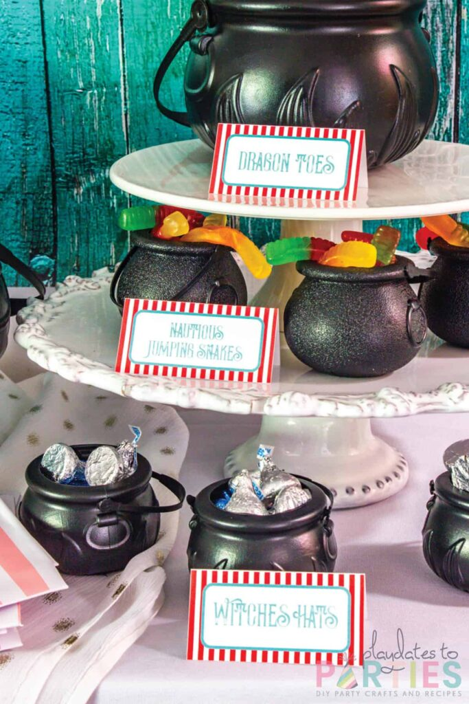 assorted candies in mini plastic cauldrons with food labels in front saying dragon toes, nautious jumping snakes, and witches hats