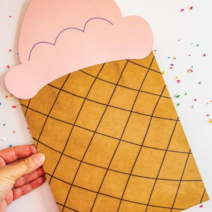 hand holding an ice cream party favor bag with a pink scoop