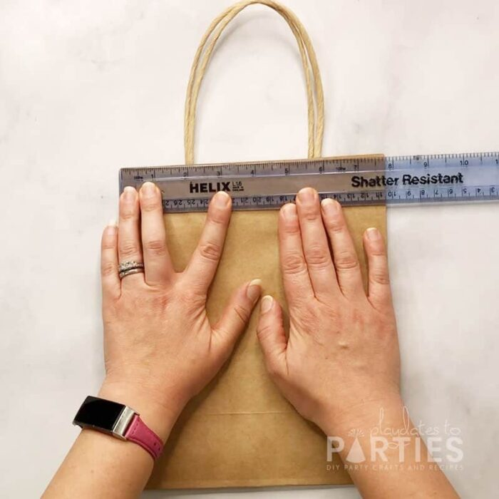 measuring the width of the brown paper bag