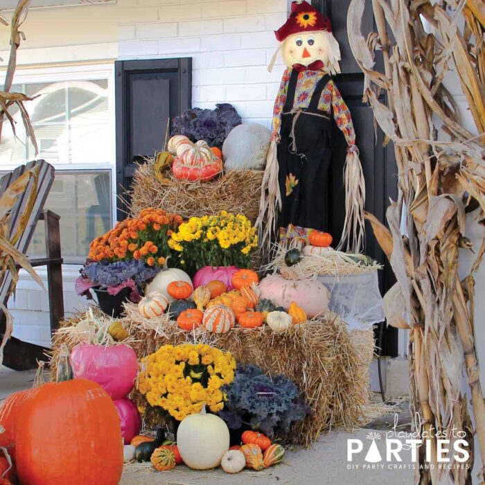 A front porch with a large display of hay bales, fall flowers, gourds, decorative lettuces, corn stalks and scarecrows