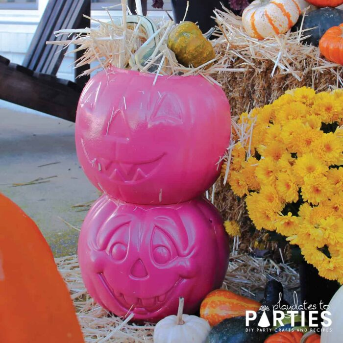Pumpkin candy baskets painted pink and filled with hay and gourds for display