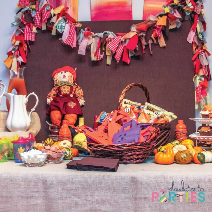 a party table with a rag garland, jack o lantern bags, scarecrows, pumkins, and fall leaf decorations