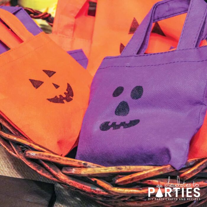 Orange and purple mini fabric bags with jack-o-lantern faces drawn on them
