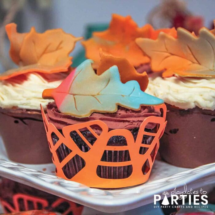 chocolate cupcakes with a candy corn wrapper and multi-colored fall leaf fondant toppers
