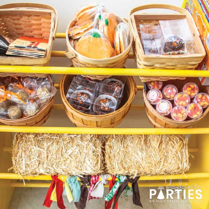 Yellow treat display with mini hay bales, bushel baskets and berry baskets filled with sweet treats