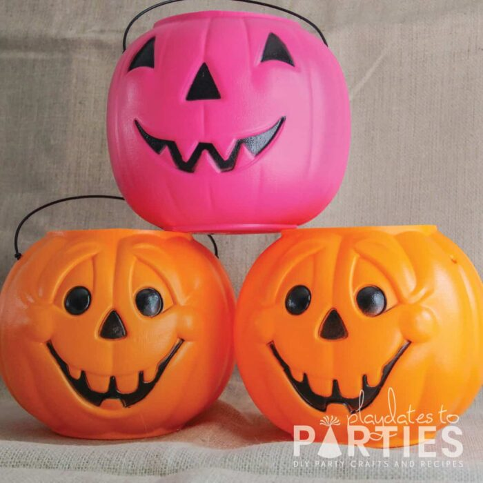plastic pumpkin candy buckets in pink and orange before being painted