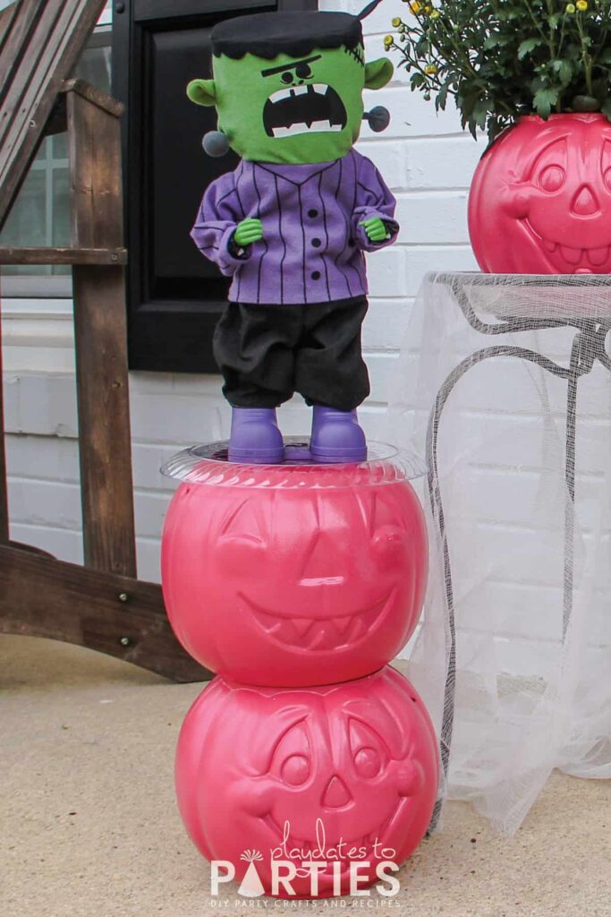 painted pumpkins stacked up to create a table with a dancing Frankenstein on top