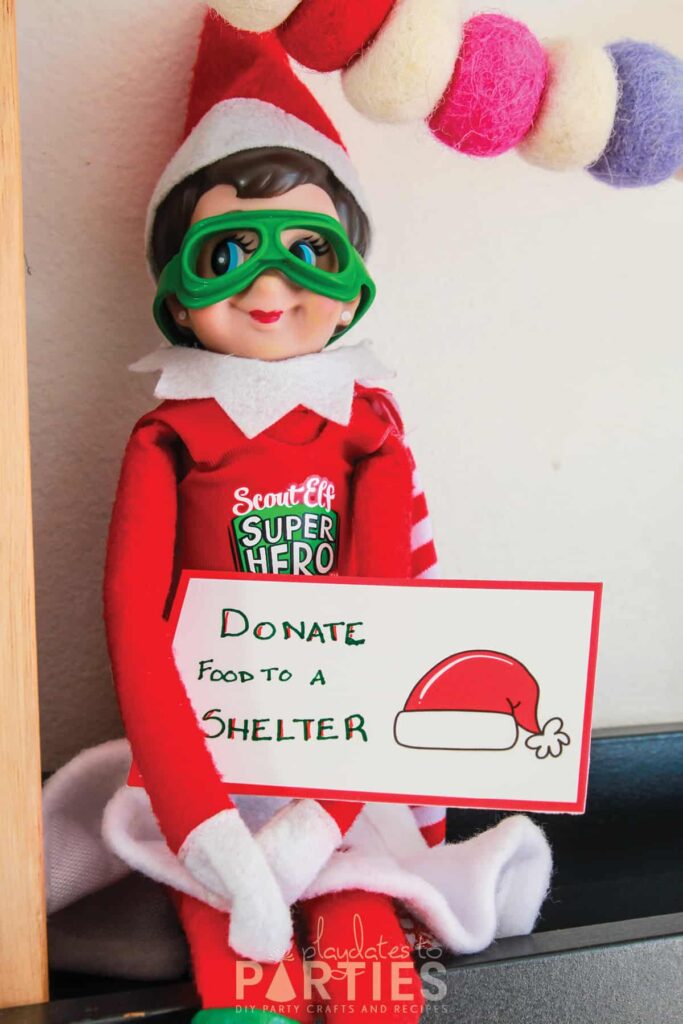 photo of elf on the shelf sitting on a ledge holding a card with a handwritten message
