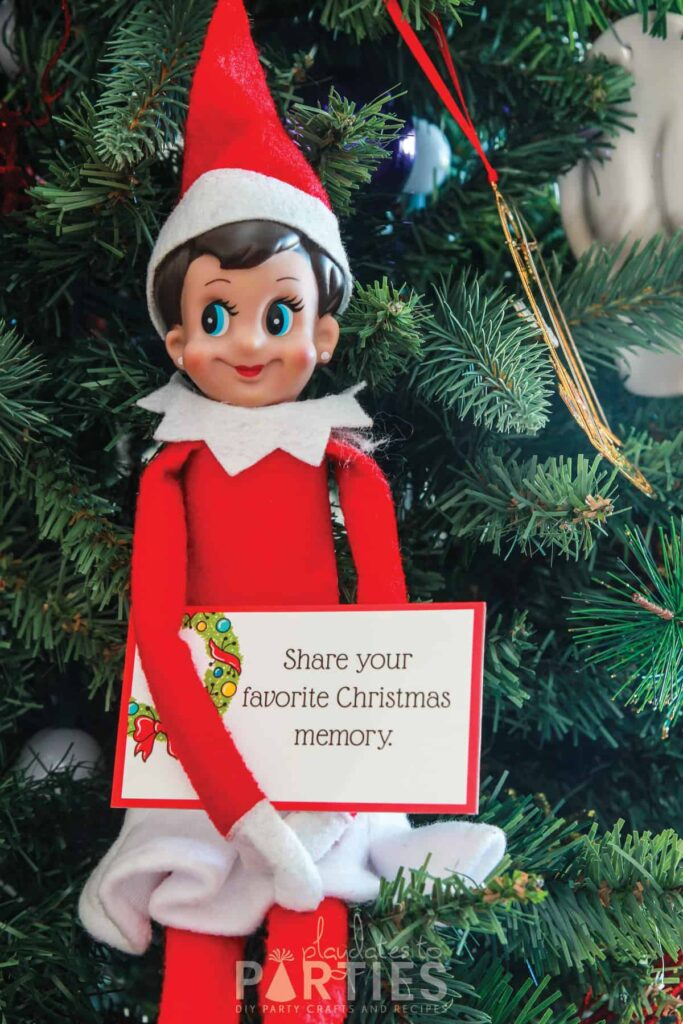 elf sitting in a Christmas tree holding a card that says share your favorite Christmas memory