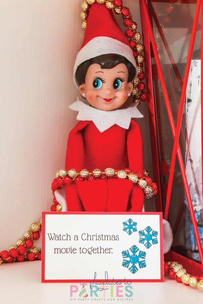 an elf sitting on a white shelf, tied up with a beaded garland with a card sitting in front that says watch a Christmas movie together