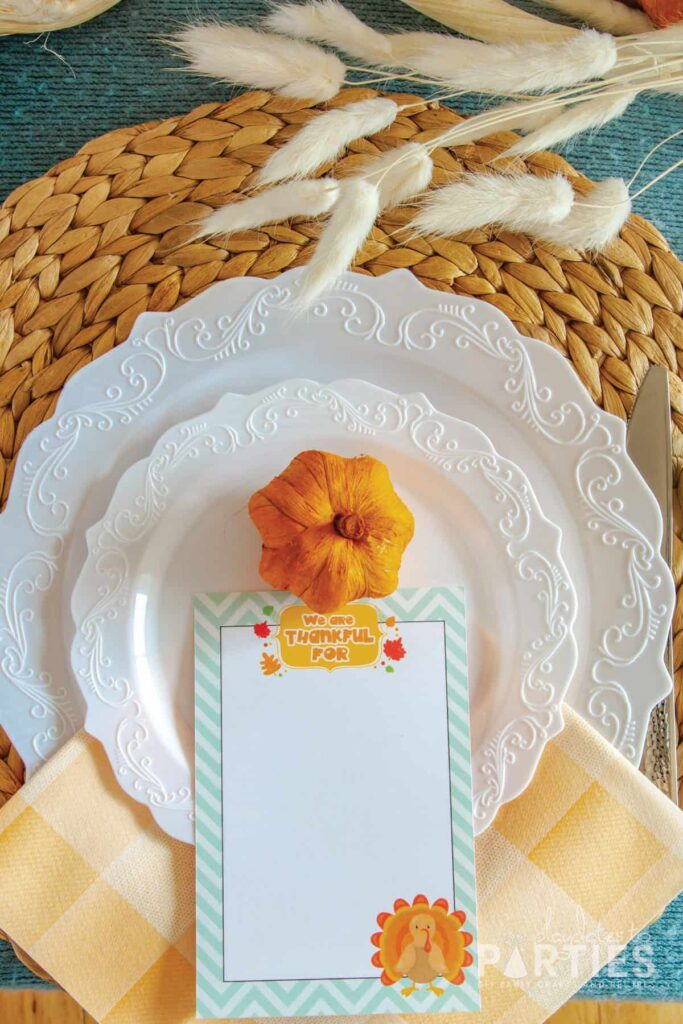 white plates on a woven hyacinth placemats with a miniature pumpkin and a we are thankful card placed on top