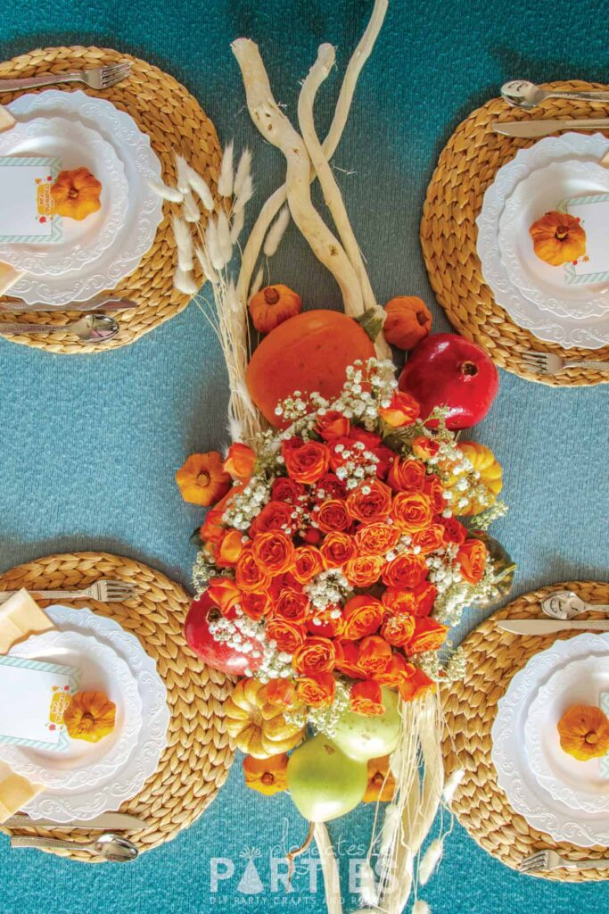 top view of a Thanksgiving table with orange roses, white plates and a blue tablecloth