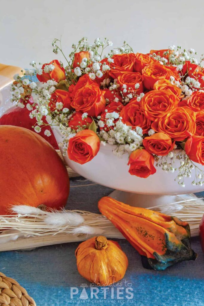 orange miniature roses with baby's breath in a white pedestal bowl on a blue tablecloth