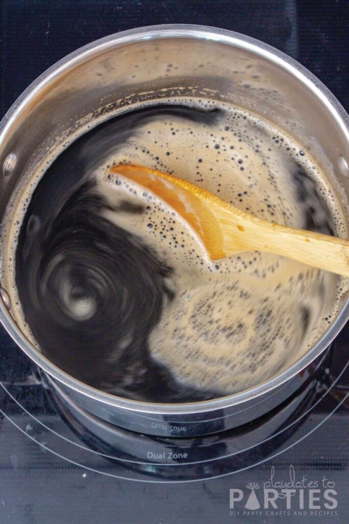 Beer syrup cooking in a pot and being stirred with a wooden spoon