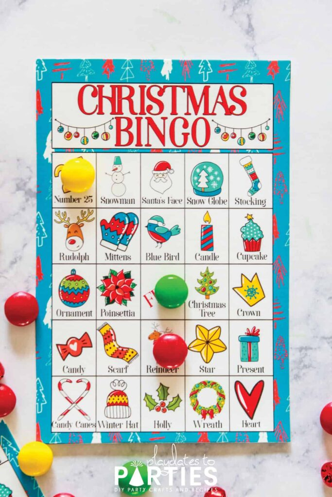a brightly colored Christmas Bingo card on a table with three spots marked by candy
