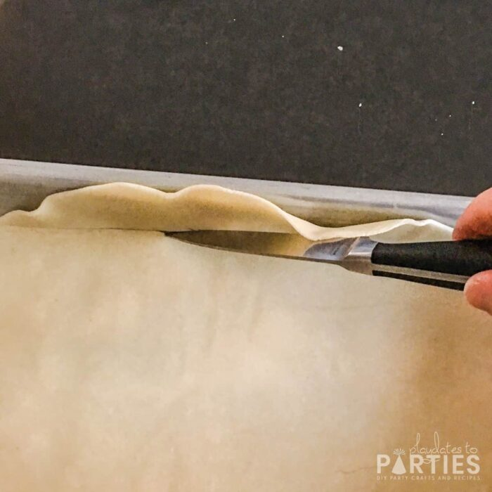 Close up of trimming pie crust at the base of a jelly roll pan
