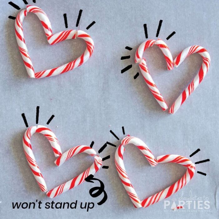 candy canes on parchment paper arranged to create hearts. But the candy canes are broken and don't all sit properly