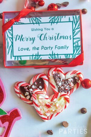 three candy cane hearts with chocolate filling on a marble counter next to a gift box with a green and white label that says Wishing You a Merry Christmas