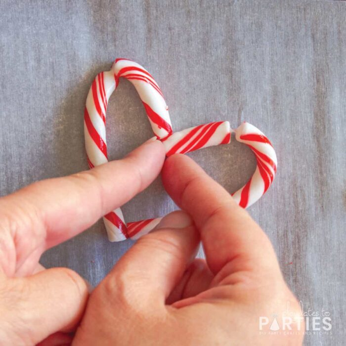 pinching together the ends of the candy cane to create a closed heart