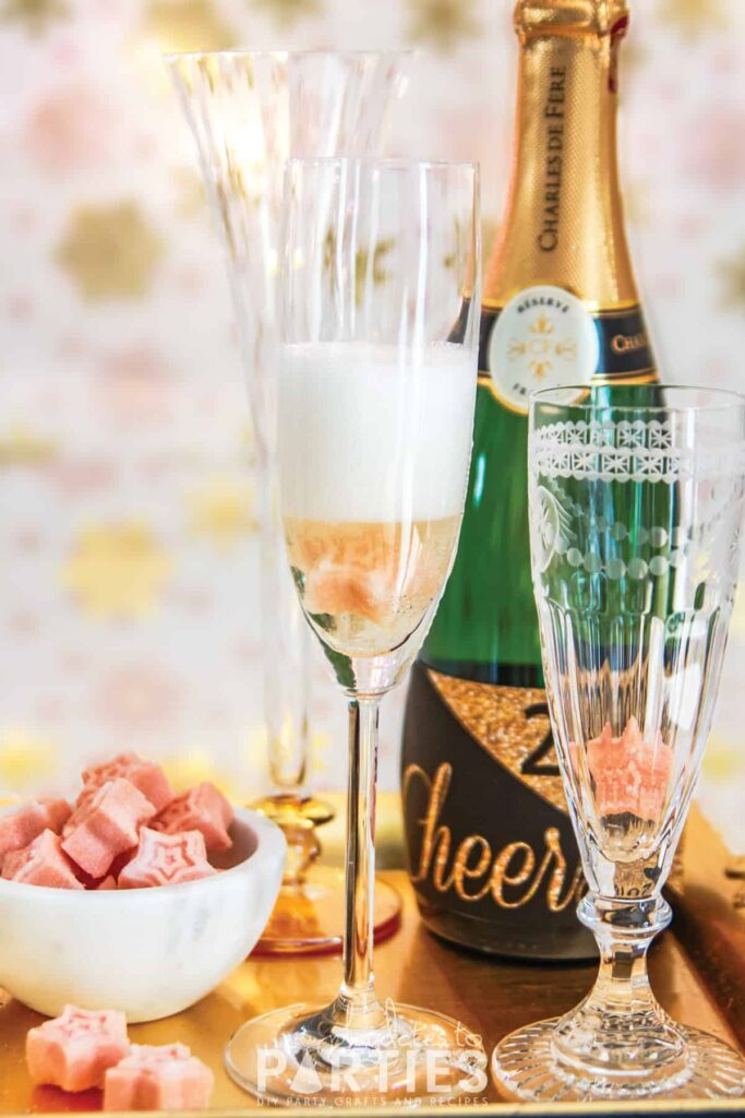 a champagne flute with a sugar cube inside and freshly poured champagne still foamy at the top