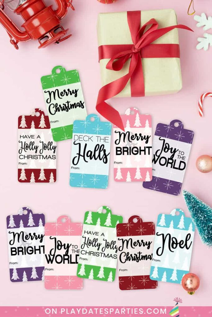 printable Christmas gift tags in assorted colors on a pink table surrounded by holiday paraphernalia