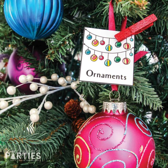 close up of a Christmas tree with a card attached that says ornaments