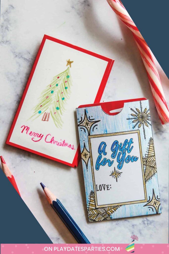 two color-in christmas gift card holders on a marble table with coloring pencils and a candy cane nearby