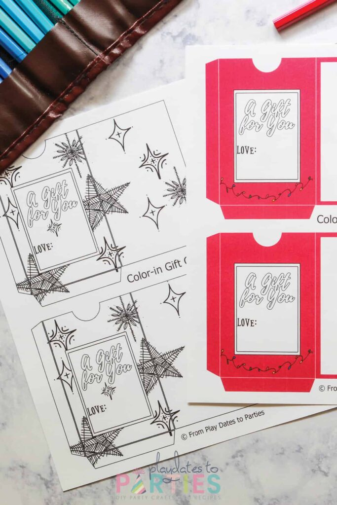 two pages of DIY gift card templates printed out, but not yet cut. One is all black and white with star shapes. One is red with a white window