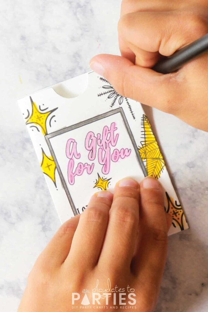 A child's hands coloring in the stars on a personalized gift card holder