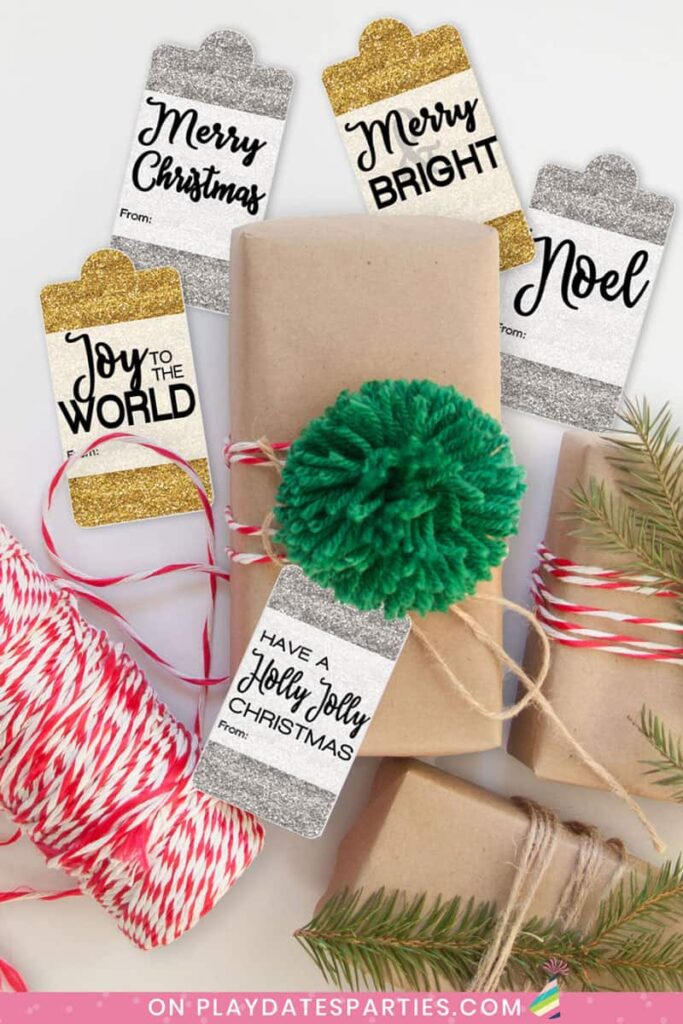 brown paper packages tied with red bakers twine and a green pompom with gold and silver glitter holiday gift tags