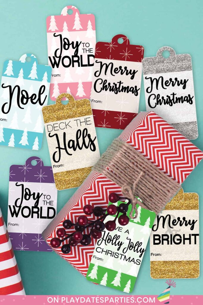 a variety of holiday gift tags on a blue table surrounding a present wrapped in red paper tied with brown twine
