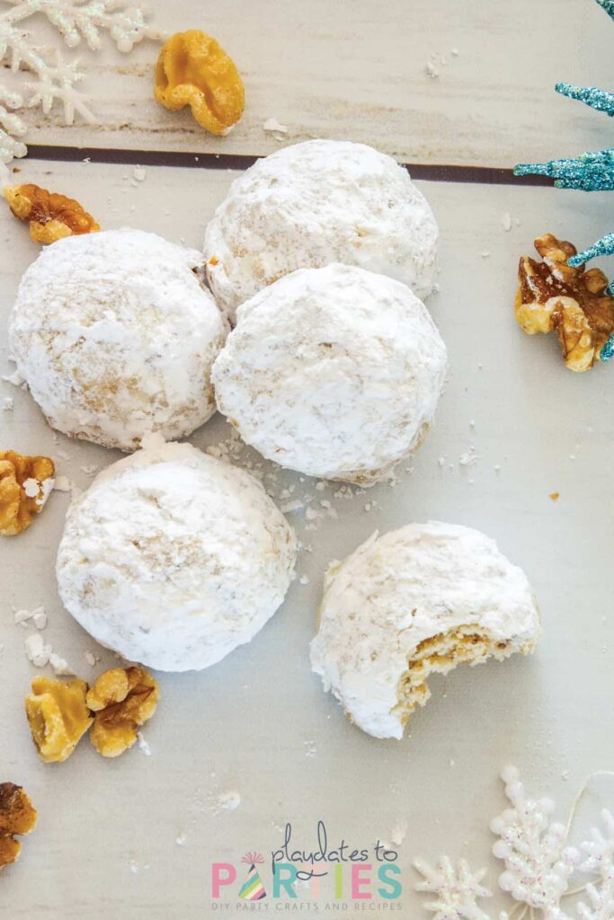 overhead photo of powdered sugar covered cookies on a white table surrounded by walnuts and snowflake Christmas ornaments
