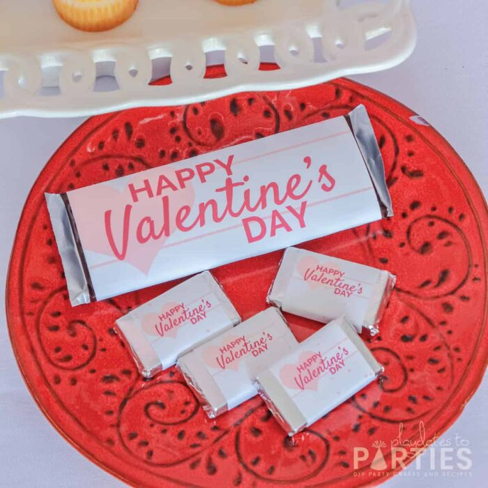 Full sized and mini candy bars with custom wrappers on a red plate