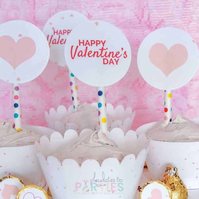 close up of cupcakes with printed wrappers and circles that have pink hearts and say Happy Valentine's Day