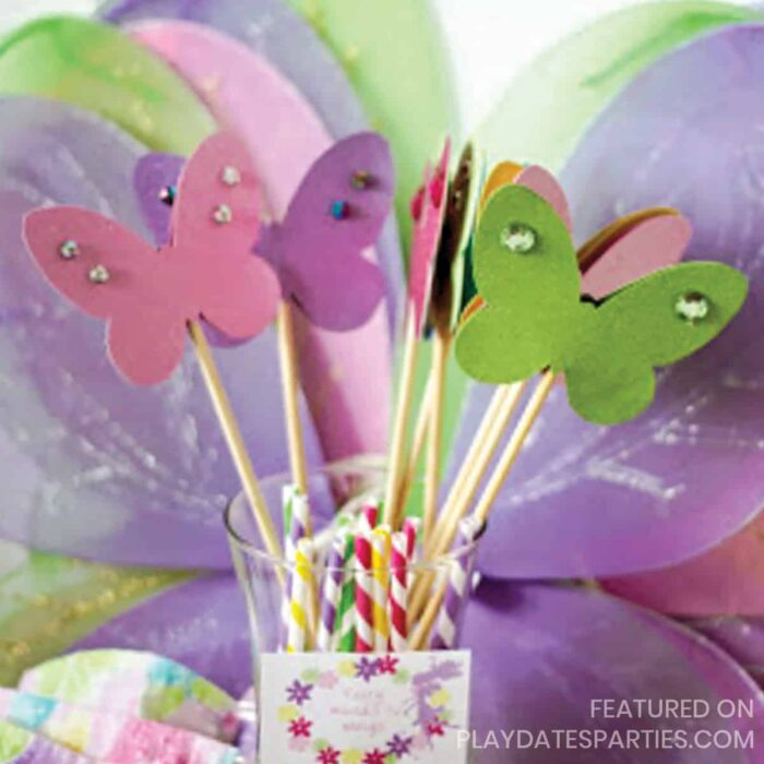 close up of purple, green, and pink butterfly wings with coordinating buttterfly wands in a vase in front.