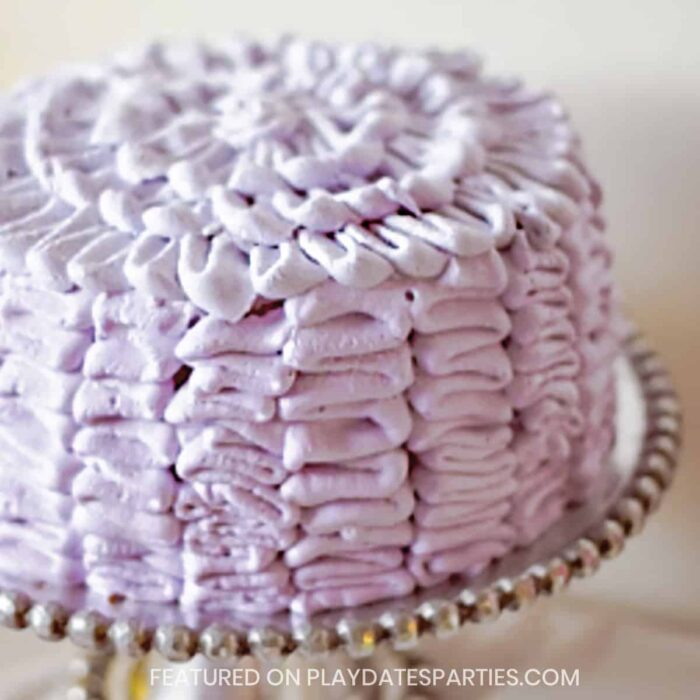 cake on a silver cake plate piped with purple frosting ruffles