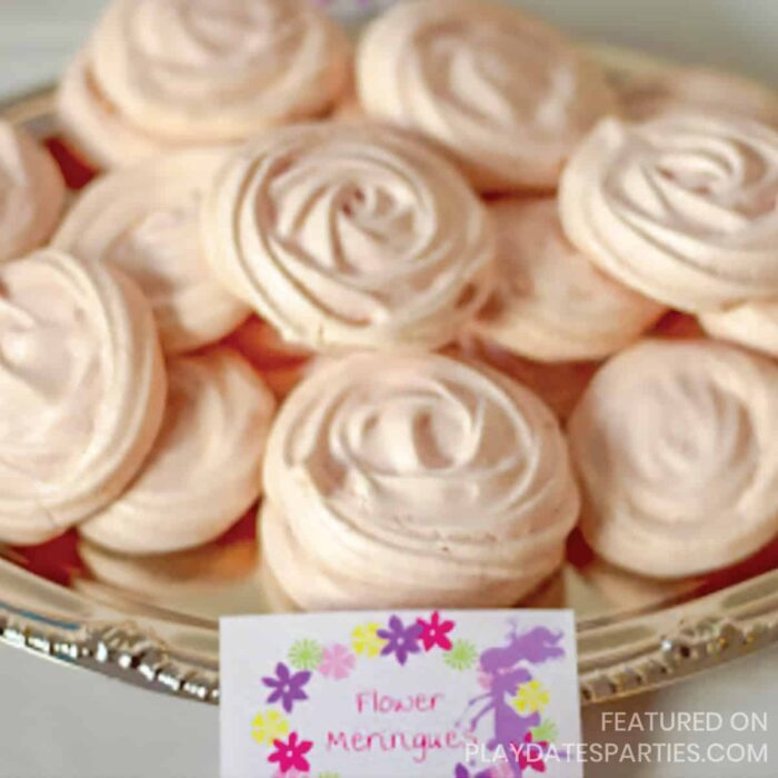 light pink meringue cookies piped to look like flowers on a silver platter with a label in front that has a fairy and flowers