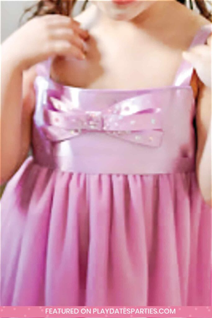 close up of a little girl's purple dress with a tutu skirt and a purple and white polka dot bow on front