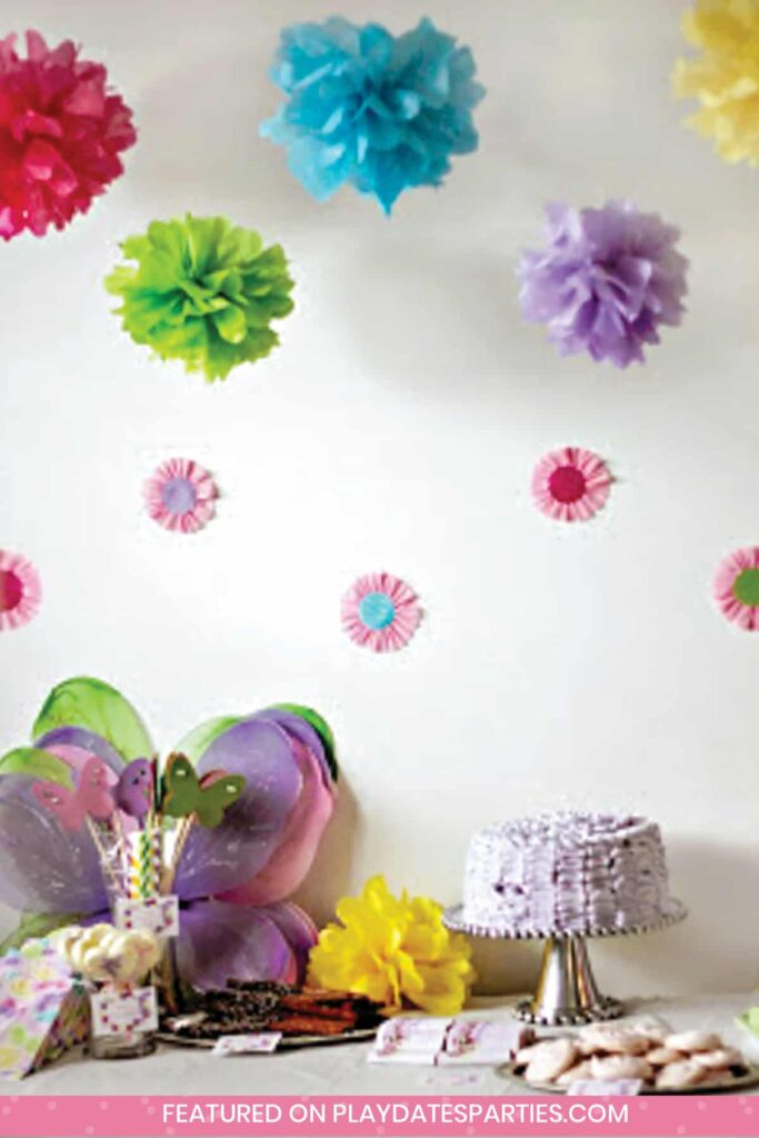 colorful tissue paper pom poms hanging over a dessert table with a cake, butterfly wings, cookies, and pretzel rods