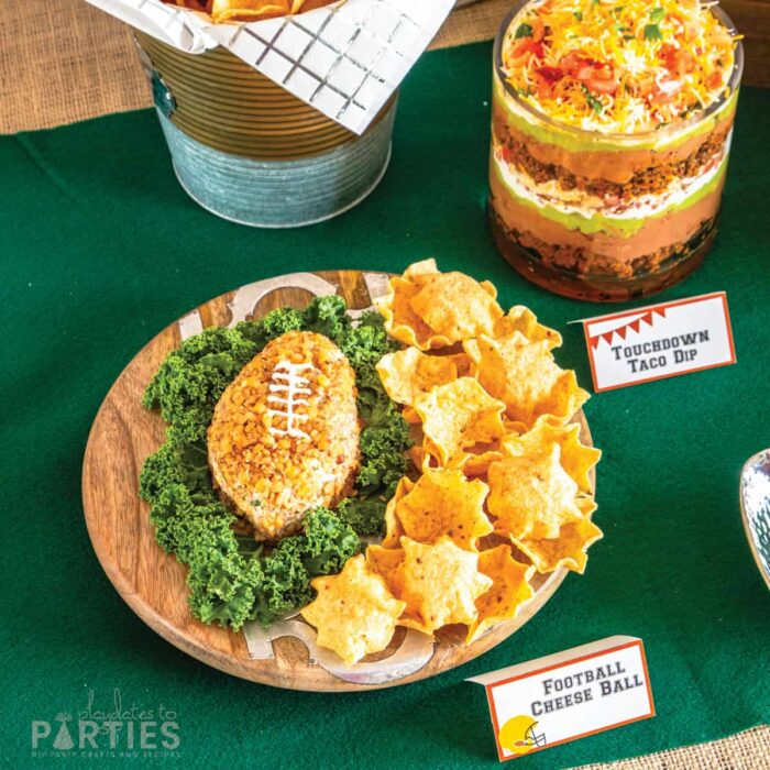 wood tray with a football shaped cheese ball on a green felt table topper